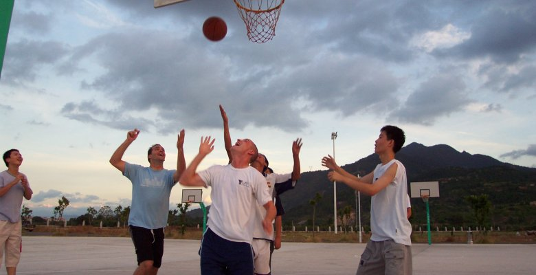 Photo of summer camp workers playing basketball with local summer camp attendees